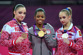Gabby Douglas posing with her Olympic gold medal